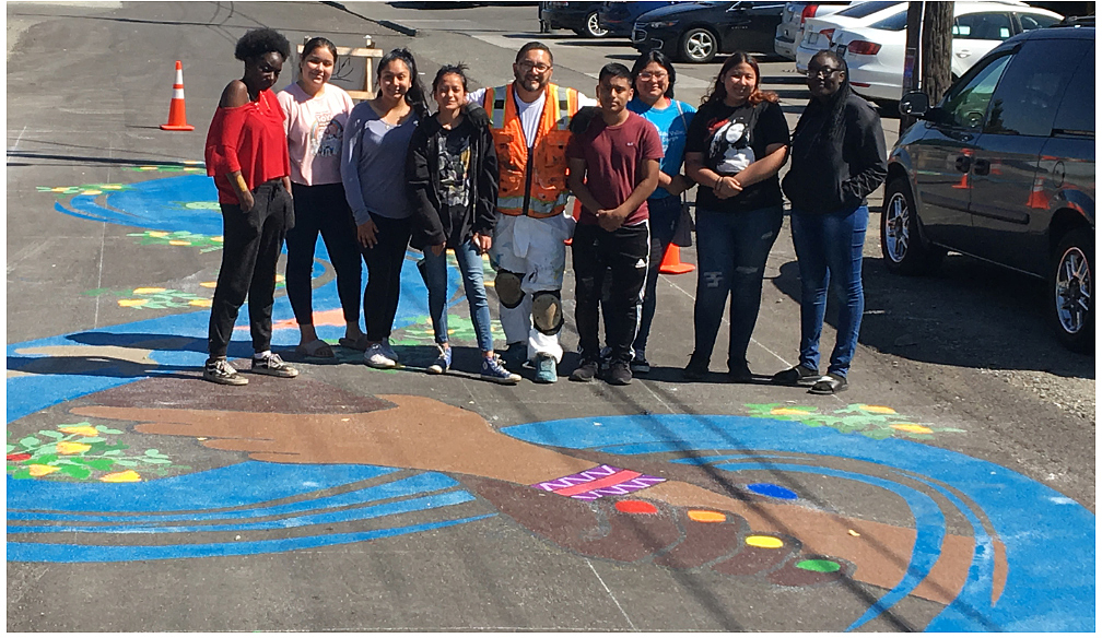 A group of youth posing next to a street mural.