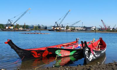 Brightly painted canoes on river shore with construction cranes in background.