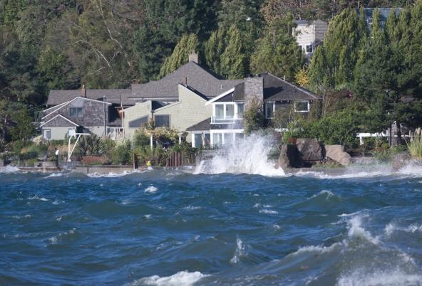 Waves crashing in front of a house. Photo: James Kinney