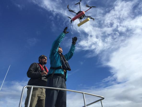 John Durban, left, pilots a small hexacopter into the hands of Holly Fearnbach. The two biologists, both with NOAA's Southwest Fisheries Science Center, use the remote-controlled aircraft to capture detailed images of killer whales. Photo: NOAA Fisheries