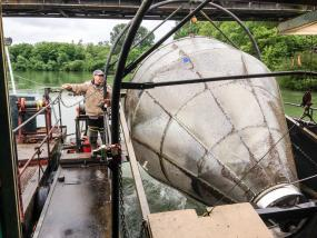 Dean Toba, a scientific technician with the Washington Department of Fish and Wildlife, operates the agency's screw trap on the Skagit River. The trap helps biologists estimate the number of juvenile salmon leaving the river each year. Photo: Christopher Dunagan, PSI