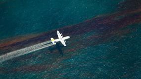 A plane releases chemical dispersant to break up an oil slick on the water surface below. Photo courtesy of the National Commission on the Deepwater Horizon Oil Spill and Offshore Drilling.