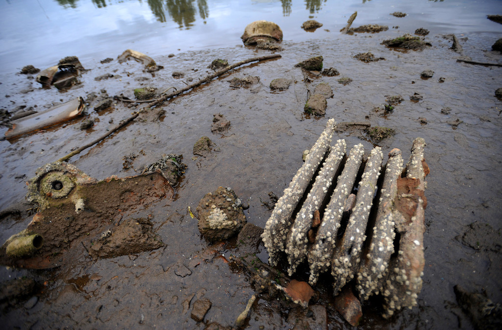 A rusty radiator and other debris in sediment of the Duwamish River at low tide.